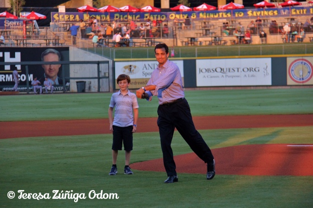Mike Suco, throws out the ceremonial first pitch as his son watches beside him.