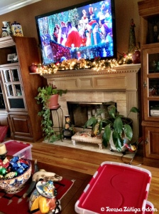 The mantle is decorated and Hallmark Christmas movies are on the TV...