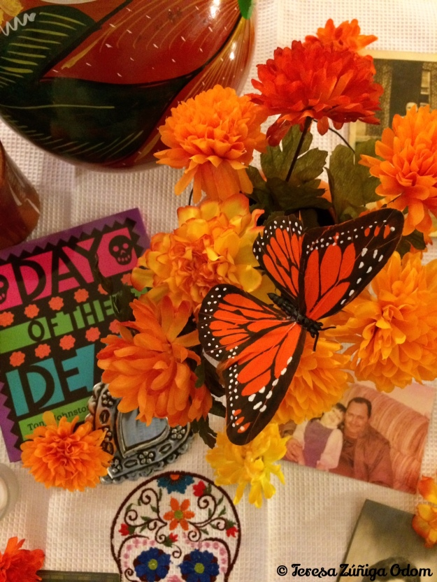 Some of the items on my Day of the Dead living room altar include a Day of the Dead book, carnations, butterflies and photos...