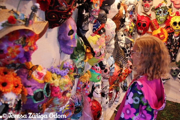 A little girl admires the sugar skull masks at Dia de los Muertos Birmingham Festival 2015