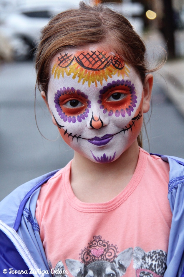 A young girl has her face painted as sugar skull at the festival.  This is one of the most popular things to do at Dia de los Muertos.