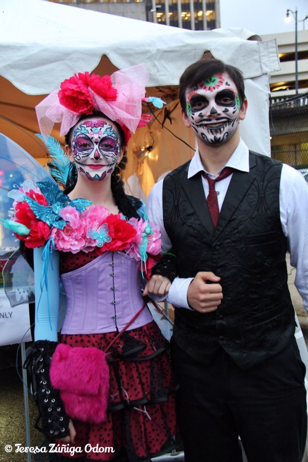 A couple dresses out in full sugar skull makeup and colorful clothing for Dia de los Muertos Birmingham 2015.
