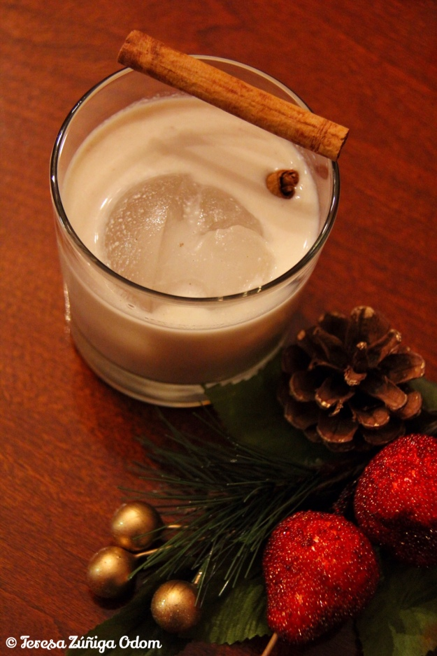 A glass of coquito garnished with two cinnamon sticks! Best served over ice and sipped in front of a Christmas tree!