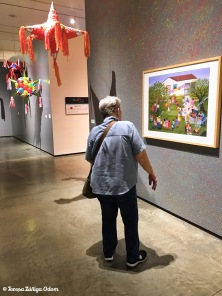 Mom admiring a painting at the exhibit.