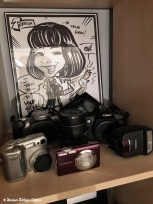 Some of my cameras...I'm a Canon girl but I did venture into Nikon territory a while back! The caricaure was made at an event I went to.