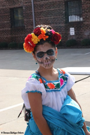Little girl in sugar skull makeup helped her mama set up in the mercado before the event opened